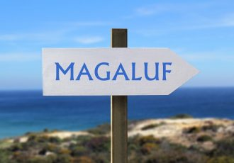 Magaluf sign with seashore in the background